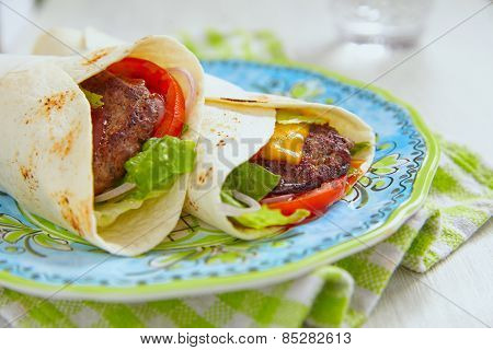 Fresh tortilla wrap with grilled beef burger