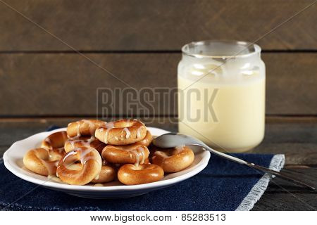 Bagels on plate with jar of condensed milk on wooden background