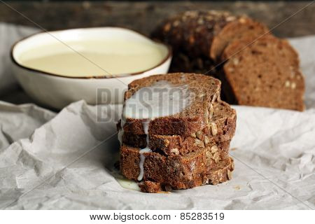 Slices of bread with condensed milk on paper background