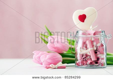Beautiful pink tulips with jar of papers  on table on bright background