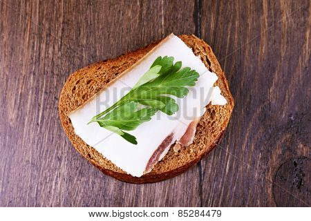 Sandwich with lard and parsley on wooden background