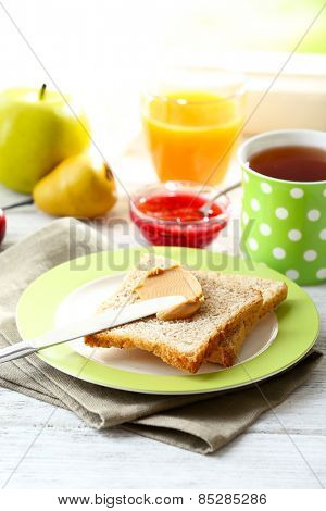 Toasts with peanut butter on plate with cup of tea and juice on light background