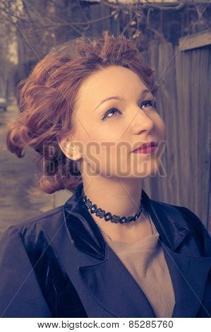 Woman with messy retro coiffure posing wearing black coat