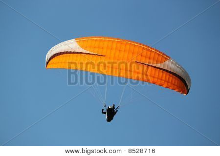 Red Paraglider In Deep Blue Sky