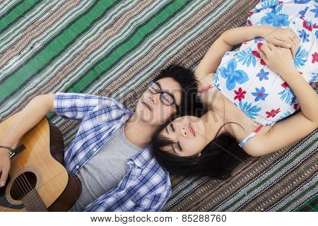 Beautiful Couple Lying On Mat With Guitar