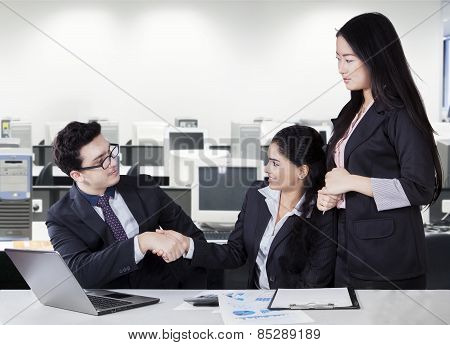 Businesspeople Shaking Hands In Office Room