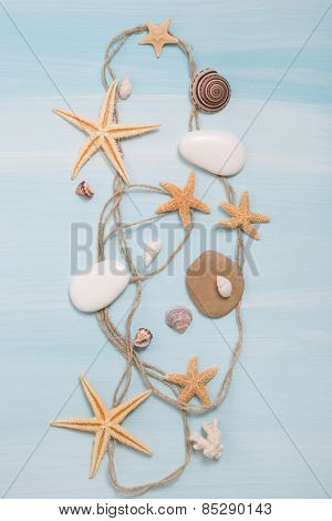 Arrangement of different shells, starfishes and stones on blue or turquoise wooden background.