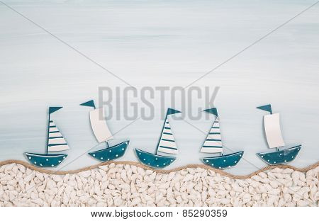Five metal handmade sailboats on a blue ocean background for summer concepts.