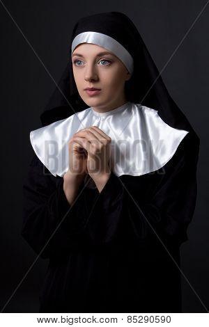 Religion Concept - Praying Nun Over Grey