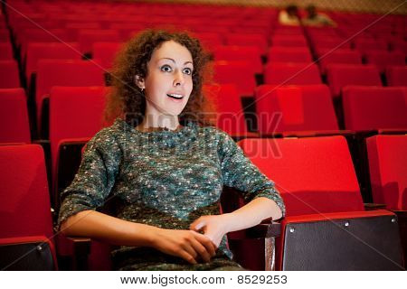 Beautiful Young Woman Sitting On Armchairs At Cinema, Steadfastly Looking