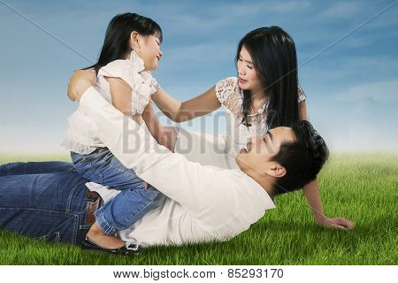 Family Playing On Green Grass