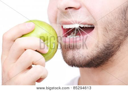 Man biting fresh green apple with healthy teeth isolated on white
