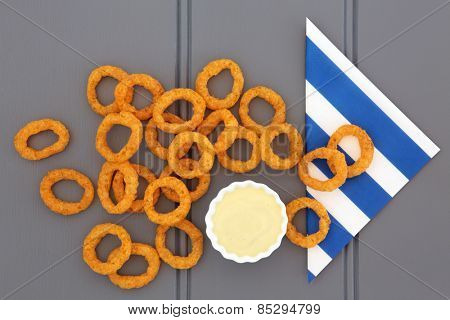 Onion ring snack food with mayo dip and striped napkin.