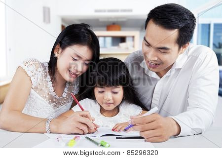 Little Girl Doing Schools Task With Parents