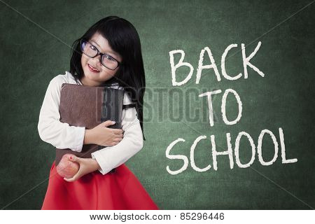 Little Girl Holds Book Back To School
