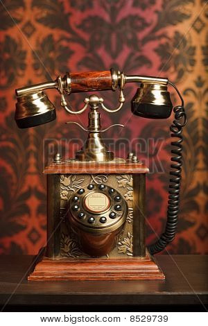 old phone is made of metal on a wooden table. withdrawn against the ornament
