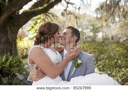 Newly married lovers in garden, groom carrying bride