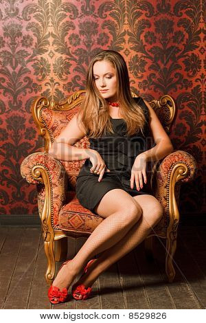 Woman in red shoes and a black dress sitting on a chair