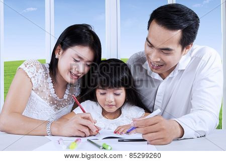 Parents Giving Homeschooling To Their Child