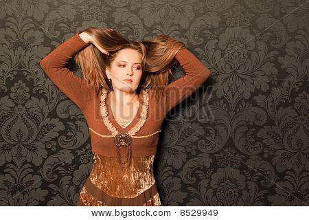 mujer en un vestido marrón que está parado al lado de una pared.