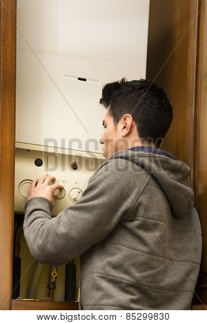 Young Man Adjusting The Boiler Or Heater