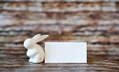 stock photo of figurine  - Small Bunny Figurine Besides Blank White Greeting Card On Top of a Wooden Table with Flurry Background - JPG