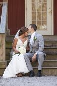 stock photo of forehead  - Young newly married couple seated on steps - JPG