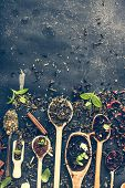 foto of black tea  - Virious kinds of tea in wooden spoons on black table - JPG