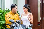 picture of say goodbye  - Woman saying goodbye to motorcyclist who is riding off to work in the morning - JPG
