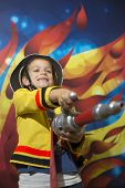 image of fireman  - Little boy dressed as a fireman holding a hose - JPG