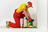 picture of carpenter  - carpenter doing parquet Wood Floor polishing maintenance work by grinding machine - JPG