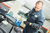 picture of auto garage  - Auto mechanic checking oil level in car engine at garage service station - JPG
