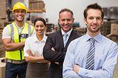 image of warehouse  - Warehouse team smiling at camera in warehouse - JPG