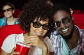 stock photo of cinema auditorium  - Young couple watching a 3d film at the cinema - JPG