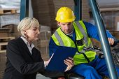 picture of forklift driver  - Forklift driver talking with his manager in a large warehouse - JPG