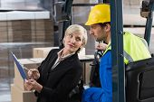 stock photo of forklift driver  - Warehouse manager talking with forklift driver in a large warehouse - JPG