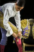 stock photo of bullfighting  - Woman bullfighter by dressing with vest on your back on a black background  - JPG