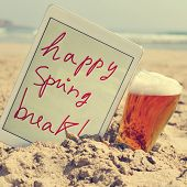 foto of spring break  - a glass with bear and a tablet with the text happy spring break written in it on the sand of a beach - JPG