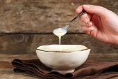 pic of condensation  - Bowl with condensed milk and spoon on napkin on wooden background - JPG