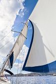 stock photo of mast  - View of the sails and mast tilt in the wind against the background of the coast on a sunny day - JPG