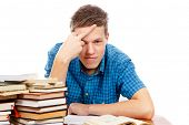image of pissed off  - a pissed off teenage student with a pile of books next to him - JPG