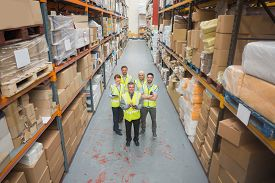 pic of warehouse  - Warehouse team smiling at camera in warehouse - JPG