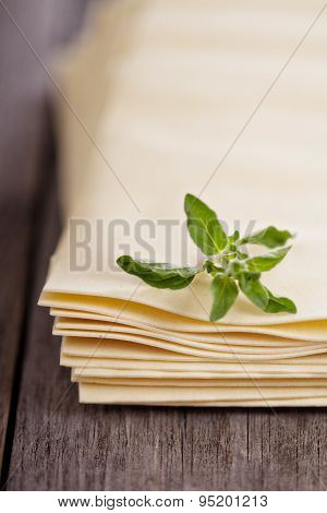 Raw lasagna sheets on wooden table