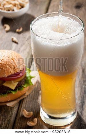 Light Beer With A Burger And Snacks