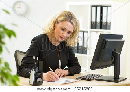 Businesswoman Writing On Her Workplace In Office Room