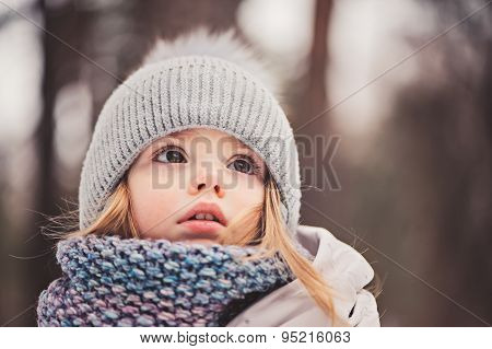 close up outdoor winter portrait of cute dreamy toddler girl in grey hat and scarf