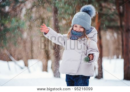 cute happy toddler girl playing with snow in winter forest