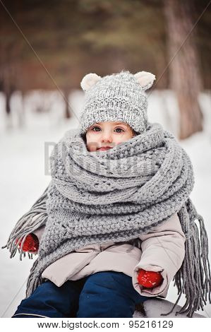 vertical winter portrait of cute baby girl in grey scarf and red gloves