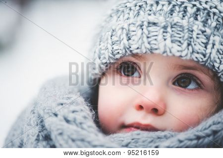 close up outdoor winter portrait of adorable happy baby girl in grey knitted hat and scarf