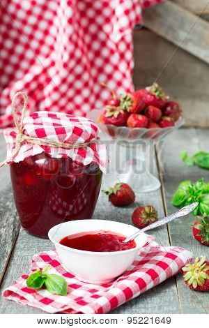 Confiture With Strawberries And Basil On A Wooden Background
